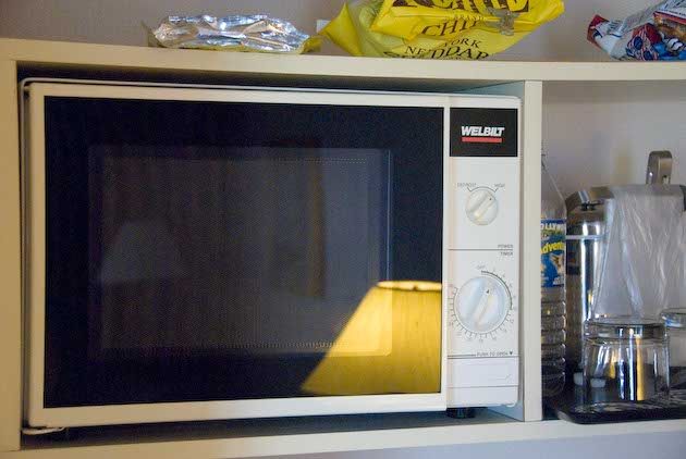 The cheap microwave oven placed on an even cheaper, sagging shelf at the Sheraton Suites hotel, Cuyahoga Falls, Ohio