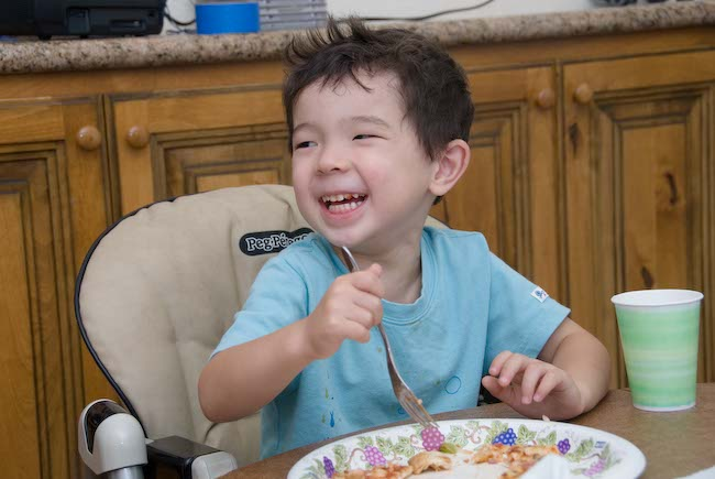 Anthony laughs while having pizza for dinner