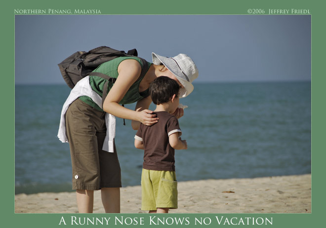 Fumie helping Anthony with his stuffy nose, at a beach on Penang Island, Malaysia; click to see Exif data and map